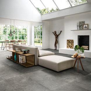 Diseño de salón abierto, moderno, grande, con paredes blancas, suelo de baldosas de porcelana, chimenea tradicional y suelo gris
