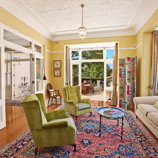 Mid-sized eclectic formal enclosed living room in Melbourne with yellow walls, light hardwood floors and no tv.
