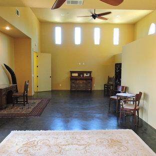 Esempio di un grande soggiorno chic aperto con sala formale, pareti gialle, pavimento in cemento, nessun camino, nessuna TV e pavimento nero