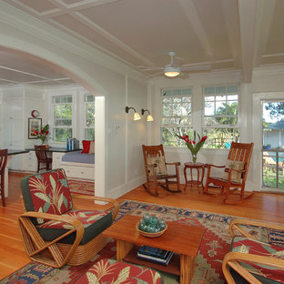This is an example of a mid-sized tropical open concept living room in Hawaii with white walls, bamboo floors, no fireplace and no tv.