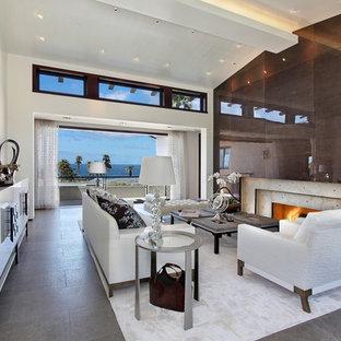 ロサンゼルスの巨大なビーチスタイルのおしゃれなLDK (白い壁、標準型暖炉、コンクリートの暖炉まわり) の写真