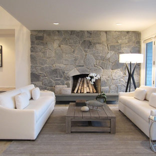 На фото: парадные, открытые гостиные комнаты среднего размера в морском стиле с бежевыми стенами, светлым паркетным полом, стандартным камином и фасадом камина из камня