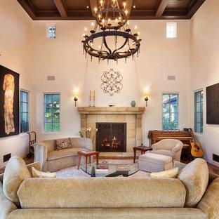 Großes Mediterranes Musikzimmer mit weißer Wandfarbe, braunem Holzboden, Kamin und Kaminumrandung aus Stein in Santa Barbara