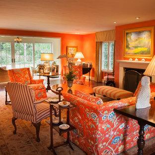 Esempio di un soggiorno chic di medie dimensioni e chiuso con sala formale, pareti arancioni, parquet scuro, camino classico, cornice del camino piastrellata, nessuna TV e pavimento marrone
