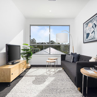 Design ideas for a scandinavian living room in Brisbane with white walls, carpet, a freestanding tv and black floor.