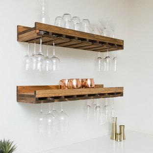 Cette image montre un salon marin de taille moyenne et ouvert avec un bar de salon, un mur gris, un sol en bois brun, une cheminée standard, un manteau de cheminée en brique, un téléviseur fixé au mur et un sol marron.