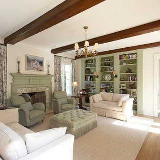 Example of a mid-sized classic formal and enclosed medium tone wood floor living room design in Dallas with white walls, a standard fireplace, a wood fireplace surround and no tv