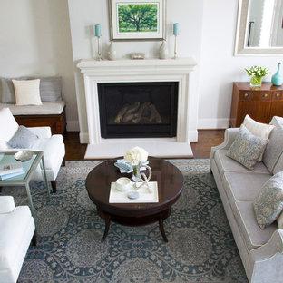 Foto di un piccolo soggiorno chic aperto con sala formale, pavimento in legno massello medio, camino classico, cornice del camino in cemento, pavimento marrone e pareti grigie
