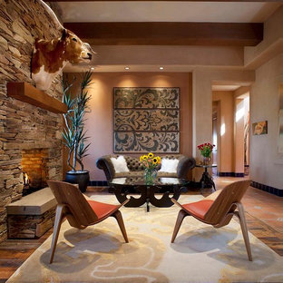 Example of a mid-sized trendy living room design in Phoenix with orange walls, a standard fireplace and a stone fireplace