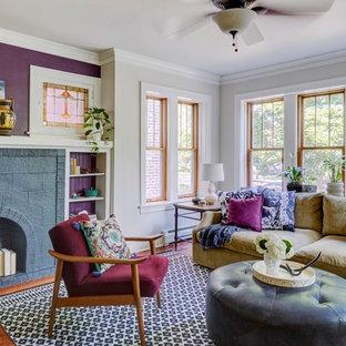 Ispirazione per un soggiorno bohémian chiuso con pareti viola, pavimento in legno massello medio, camino classico, cornice del camino in mattoni e pavimento marrone