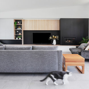 Photo of a large contemporary formal open concept living room in Geelong with white walls, ceramic floors, a wood fireplace surround, a wall-mounted tv, grey floor and a standard fireplace.