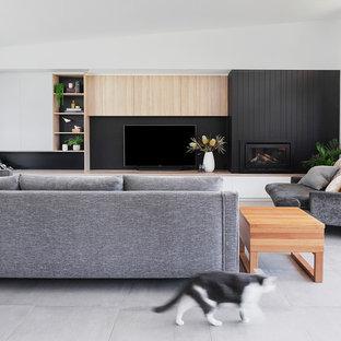 Esempio di un grande soggiorno minimal aperto con pareti bianche, pavimento con piastrelle in ceramica, cornice del camino in legno, TV a parete, pavimento grigio, sala formale e camino classico