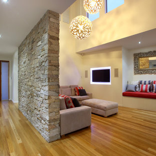 Inspiration for a contemporary medium tone wood floor living room remodel in Brisbane with beige walls and a wall-mounted tv