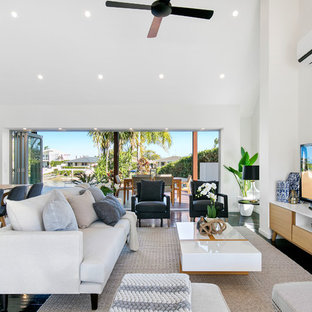 This is an example of a coastal formal open plan living room in Brisbane with white walls, a freestanding tv and black floors.