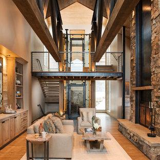 Foto di un soggiorno stile rurale aperto con pareti beige, pavimento in legno massello medio, camino classico, cornice del camino in pietra e pavimento marrone