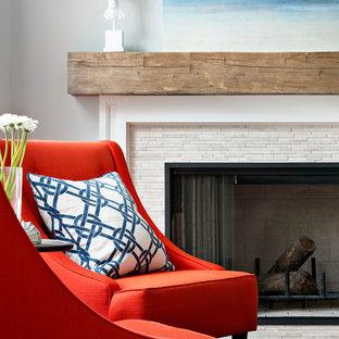 Foto de biblioteca en casa abierta, costera, de tamaño medio, con suelo de madera en tonos medios, chimenea tradicional, televisor colgado en la pared, marco de chimenea de piedra y paredes azules