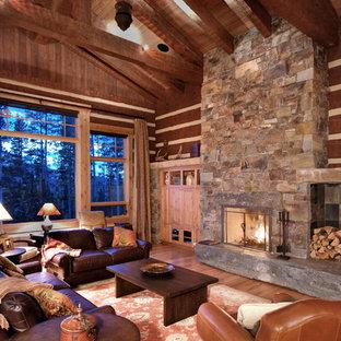 Modelo de salón para visitas abierto, rústico, de tamaño medio, con suelo de madera clara, marco de chimenea de piedra y paredes marrones
