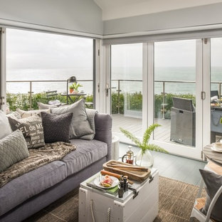 コーンウォールの小さいビーチスタイルのおしゃれなLDK (フォーマル、白い壁、塗装フローリング、薪ストーブ、タイルの暖炉まわり、壁掛け型テレビ、グレーの床) の写真