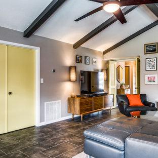 オースティンの中サイズのミッドセンチュリースタイルのおしゃれなLDK (ライブラリー、グレーの壁、磁器タイルの床、据え置き型テレビ、茶色い床) の写真