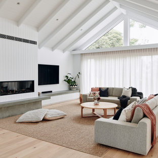 This is an example of a large contemporary open concept living room in Melbourne with white walls, light hardwood floors, a standard fireplace, a plaster fireplace surround, a wall-mounted tv, beige floor, recessed and panelled walls.