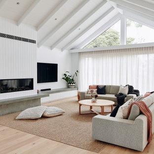 メルボルンの広いコンテンポラリースタイルのおしゃれなLDK (白い壁、淡色無垢フローリング、標準型暖炉、漆喰の暖炉まわり、壁掛け型テレビ、ベージュの床、折り上げ天井、パネル壁) の写真