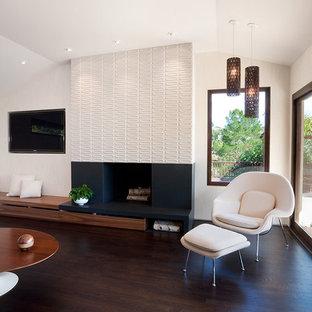 Пример оригинального дизайна: открытая гостиная комната в стиле ретро с фасадом камина из плитки, бежевыми стенами, темным паркетным полом, стандартным камином и коричневым полом