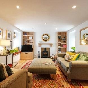 Foto de salón para visitas cerrado, de estilo de casa de campo, de tamaño medio, con paredes blancas, suelo de madera clara, estufa de leña, marco de chimenea de metal y televisor independiente