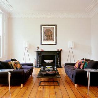 ニューヨークの北欧スタイルのおしゃれな独立型リビング (フォーマル、白い壁、淡色無垢フローリング、標準型暖炉、オレンジの床) の写真