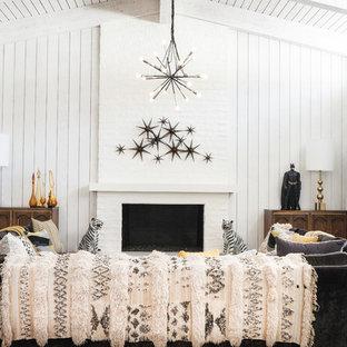 Modelo de salón vintage con paredes blancas, chimenea tradicional, marco de chimenea de ladrillo y suelo gris