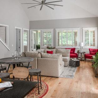 Esempio di un piccolo soggiorno stile americano stile loft con pareti grigie, parquet chiaro e TV a parete