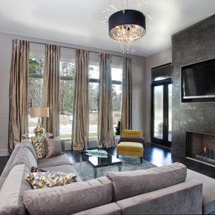 Imagen de salón actual con marco de chimenea de baldosas y/o azulejos y suelo negro