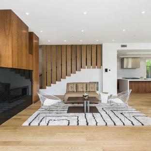 Idée de décoration pour un très grand salon vintage ouvert avec une salle de réception, un mur blanc, un sol en bois clair, une cheminée ribbon, un manteau de cheminée en pierre, aucun téléviseur et un sol beige.