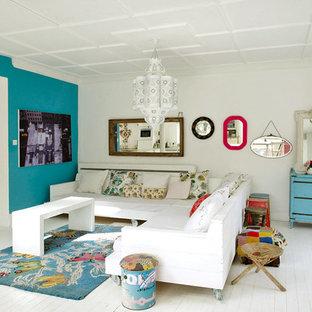 Foto på ett eklektiskt vardagsrum, med blå väggar och målat trägolv