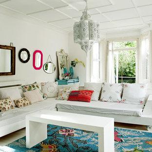 Eklektisk inredning av ett vardagsrum, med vita väggar, målat trägolv och en öppen vedspis