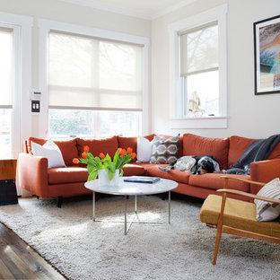 Aménagement d'un grand salon rétro ouvert avec un mur blanc, un sol en bois brun, aucune cheminée, aucun téléviseur et un sol marron.