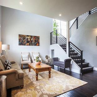 Immagine di un soggiorno minimal di medie dimensioni e stile loft con pareti grigie, parquet scuro e TV nascosta
