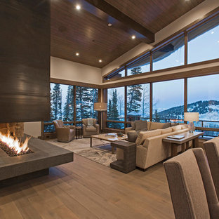 Idee per un ampio soggiorno design aperto con sala formale, pareti grigie, pavimento in legno massello medio, camino bifacciale, cornice del camino in metallo e nessuna TV