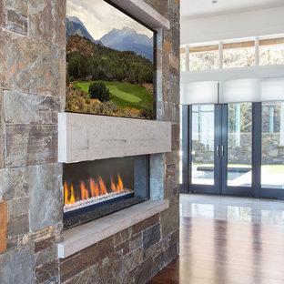 Esempio di un ampio soggiorno design aperto con sala formale, pareti bianche, parquet scuro, camino bifacciale e cornice del camino in pietra