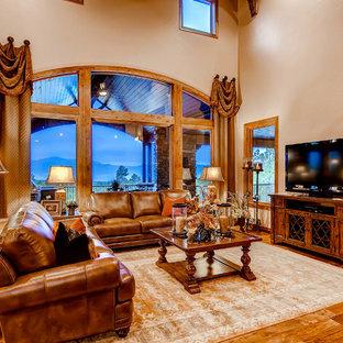 Ispirazione per un grande soggiorno stile americano aperto con sala formale, pavimento in legno massello medio, camino classico, cornice del camino in pietra e TV autoportante