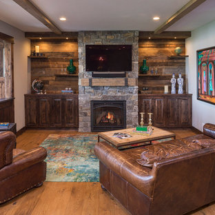 Mountain style medium tone wood floor and brown floor living room photo in Minneapolis with brown walls, a standard fireplace, a stone fireplace and a wall-mounted tv