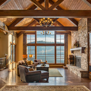 Rustic open plan living room in Other with dark hardwood flooring, a standard fireplace, a stone fireplace surround and brown floors.
