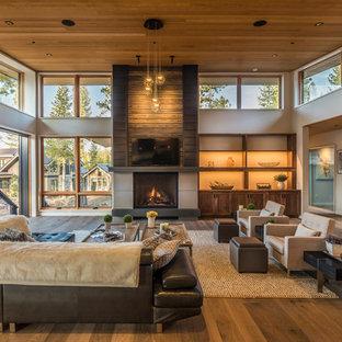 Foto de salón abierto, rústico, con suelo de madera en tonos medios, chimenea tradicional, televisor colgado en la pared y paredes grises