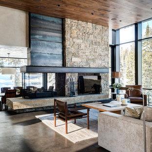 Modelo de salón abierto y piedra, contemporáneo, extra grande, con paredes beige, suelo de cemento, chimenea de doble cara, marco de chimenea de piedra y televisor independiente