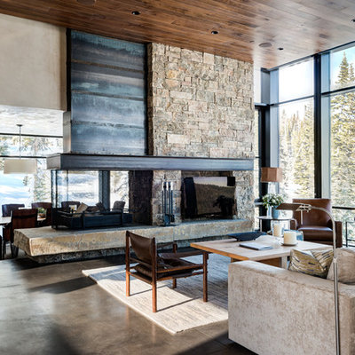 Inspiration for a huge contemporary open concept concrete floor living room remodel in Other with beige walls, a two-sided fireplace, a stone fireplace and a tv stand