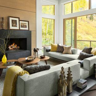 Modelo de salón abierto, moderno, grande, sin televisor, con paredes blancas, chimenea tradicional y suelo de madera clara