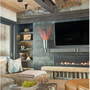 Ejemplo de salón con barra de bar abierto, rústico, grande, con chimenea lineal, marco de chimenea de piedra, televisor colgado en la pared, paredes beige, suelo de madera en tonos medios y suelo marrón