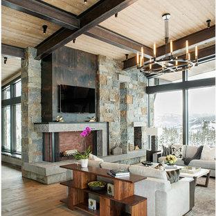 Imagen de salón para visitas abierto, moderno, grande, con suelo de madera en tonos medios, chimenea de esquina, marco de chimenea de piedra, televisor colgado en la pared y suelo marrón