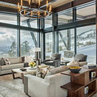Ejemplo de salón para visitas abierto, moderno, grande, con suelo de madera en tonos medios, chimenea de esquina, marco de chimenea de piedra, televisor colgado en la pared y suelo marrón