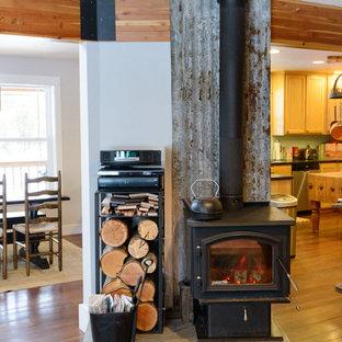 Foto di un soggiorno boho chic aperto con pavimento in legno massello medio e stufa a legna