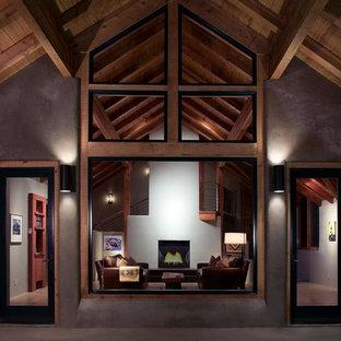 Idee per un soggiorno minimal aperto con pareti grigie, parquet scuro, camino bifacciale, cornice del camino in cemento, nessuna TV e pavimento marrone